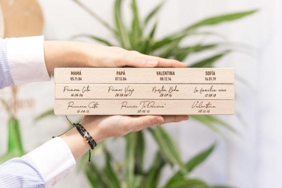 """DESCRIPCIÓNENVÍOS Y DEVOLUCIONESPREGUNTASVALORACIONES (0) DESCRIPCIÓN DEL PRODUCTO Base de fotos personalizable """"momentos"""" by Kuko – Base de madera maciza de haya cortada y fabricada a mano. Nuestra base de fotos está fabricada con madera procedente de un bosque certificado PEFC (certificado que garantiza que la madera proviene de bosques gestionados sosteniblemente, evitando la corta ilegal y fomentando las principales funciones que juegan los recursos forestales). 100% Natural. Fabricamos nuestras bases para fotos a partir de un bloque de haya maciza, al cual damos forma cortando y puliendo cada uno de sus lados y esquinas. Totalmente exento de barnices o tratamientos químicos, el acabado suave al tacto es gracias al pulido de cada una de sus caras, por lo que el material puede ser algo poroso. Puedes lavar con un trapo húmedo el polvo o suciedad que pueda acumular día a día. Los detalles. Materiales y Especificaciones: • Medidas de la base para fotos: 29 cm largo x 2,5 cm alto x 4,5 cm de ancho • Madera Noble de Haya maciza con acabado natural pulido, sin barnices ni químicos. • La fotografías que se muestran el las imágenes no están incluidas. Por favor, ten en cuenta que el texto y el diseño grabado será como muestran las fotografías con el mismo estilo que se muestra en las fotografías. Al tratarse de madera natural, la pieza puede presentar vetas o tonalidades ligeramente distintas a las que muestra la imágen. Así mismo, el grabado puede variar su profundidad y color en función del veteado de la misma madera. Un consejo, revisa bien tus textos y ortografía antes de realizar el pedido ya que el texto que escribas será tal cual lo grabemos así que asegurate que esté todo correcto. Marca la opción del menú si quieres que imprimamos 4 fotos como las que muestran nuestras imágenes. Tienes 4 campos para adjuntarlas. Las encuadraremos en formato polaroid o Pocket para que puedas exponerlas en tu base. Ten en cuenta que imprimiremos las fotos en la calidad que nos en"""